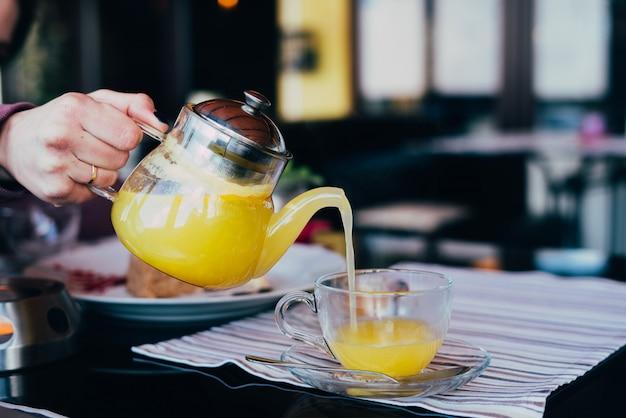 女性がお茶のガラスのティーポットを注ぐ