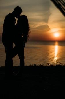 愛の美しいカップル、夜明けの観光客がお互いの目を見て笑顔
