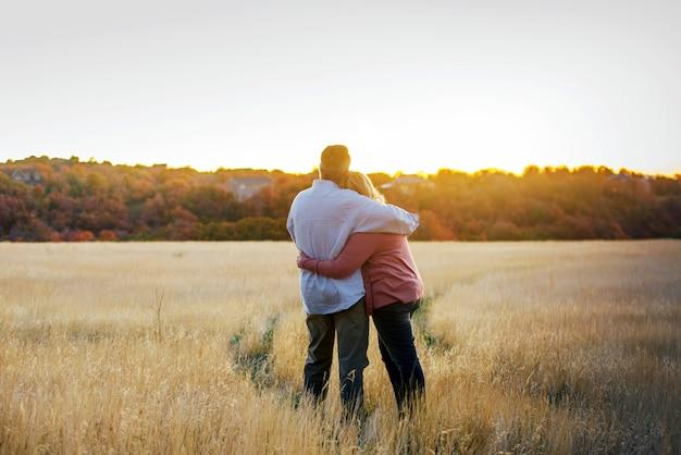 水平方向の夕日を見てお互いをハグ大人のカップルを愛する