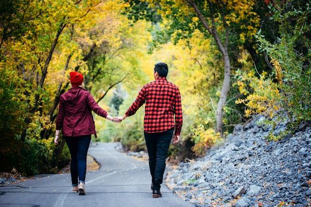 秋の道を歩いて手を繋いでいるカップル