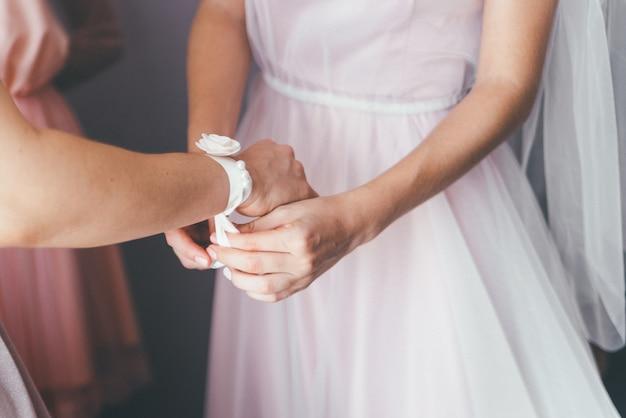 Крупный план невесты надевает аксессуары для прислуги