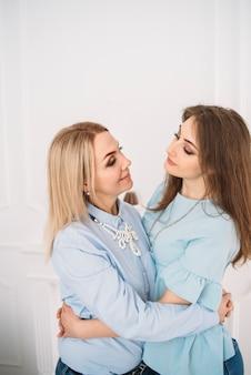 Мать и взрослая дочь обнимаются красивые глядя друг на друга