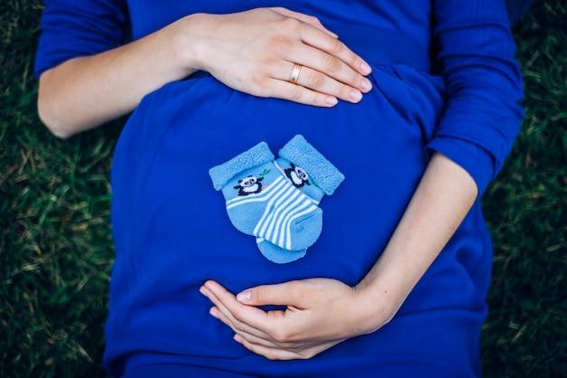 ソックスで腹を持って草の上に横たわる妊娠中の女性
