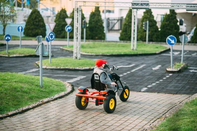 小さな男の子は庭でおもちゃの車を運転しています。