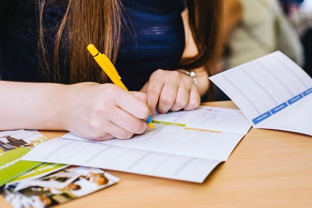 女の子は木製のテーブルの上の青いシャツに黄色のペンでフォームを書いています