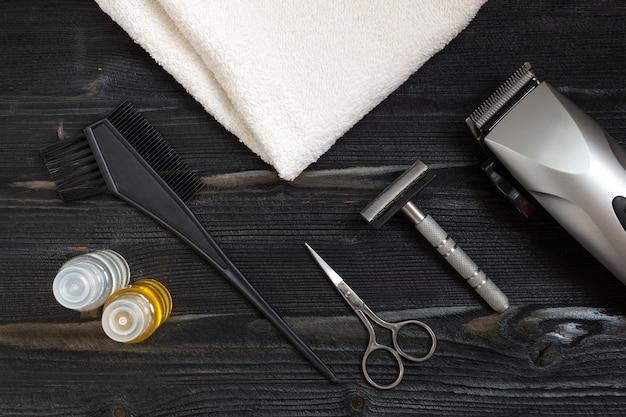 家庭用および理髪店用の理髪機器。シェービングキット、石鹸、白いタオルで木製の表面に横たわっているはさみの平面図です。