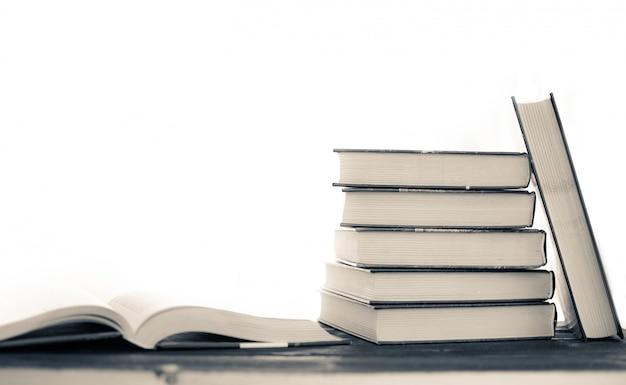 珍しい本の山。開いた本、木製のテーブルのハードカバーの本。