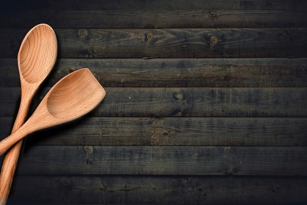 暗い木製のまな板またはデスクテーブルトップビューフラットレイアウト背景に木製キッチンスプーン