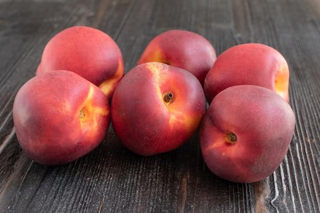 Персики на темной деревянной поверхности стола