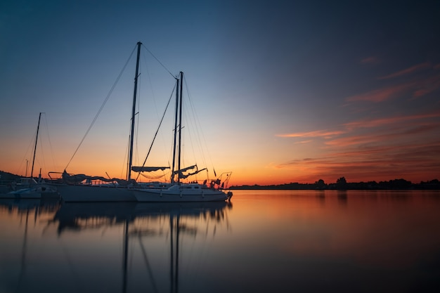 休日休暇旅行の概念:休日休暇日没日の出帆岸壁のヨット。航海、リラクゼーション