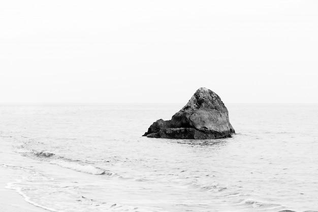 Одинокая скала. минималистский монохромный морской пейзаж