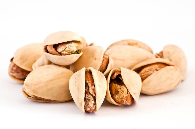 Соленые орехи жареного фисташки на изолированном фоне