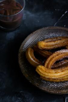 秋の朝の砂糖とホットチョコレートの典型的なチュロス