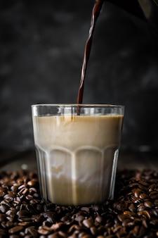 コーヒー豆の背景を持つミルクのガラスにコーヒーを注ぐ
