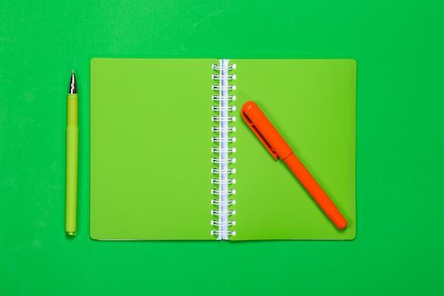 Зеленый блокнот и две ручки на цветном фоне