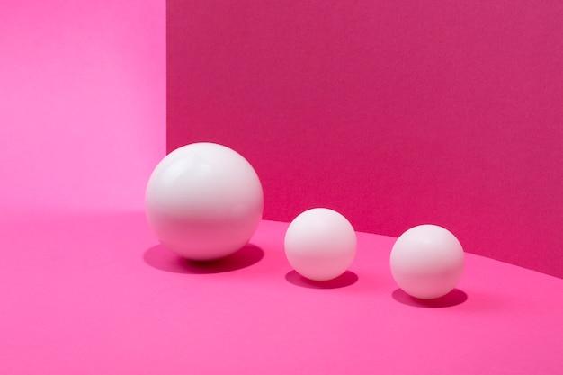 Абстрактный натюрморт с белыми шарами на розовом фоне