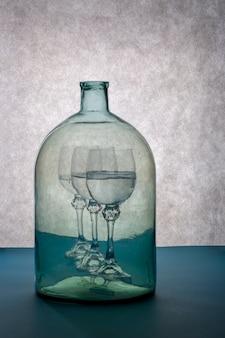 メガネと大きな透明なボトルのある静物ミラージュ