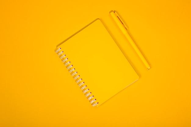 Желтая тетрадь и ручка на желтой предпосылке.