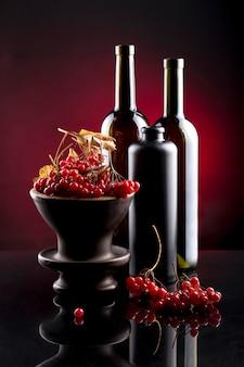 ガマズミ属の木の赤い果実と瓶のある静物