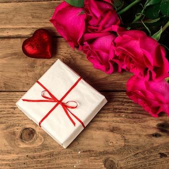 Романтическая композиция с розовыми цветами и подарком ко дню святого валентина