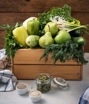 Веганская еда. свежие зеленые овощи в деревянной коробке