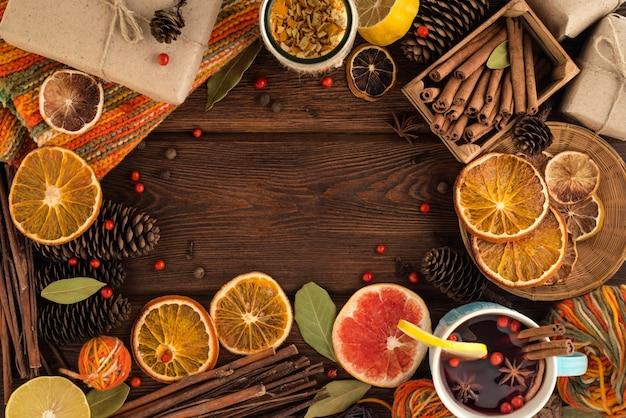 パン屋さんの居心地の良い静物セット:グリューワイン、シナモン、アニス、レモン、ドライシトラス。クリスマスベーカリーコンセプトの背景。青いセラミックガラスの温かいサイダー、ニットの温かい織物、所定の箱。