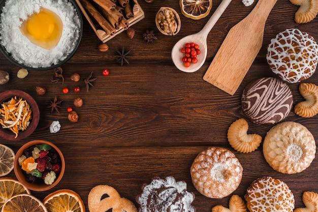 クリスマスベーカリーコンセプトの背景。ベーカリーセットと居心地の良い静物:自家製クッキー、ケーキ、ナッツ、シナモン、フレーバー、卵クランベリー、レモン、暗い木製のテクスチャの乾燥柑橘類。