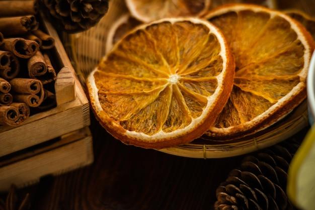 クリスマスベーカリーと新年のコンセプト。乾燥したオレンジの柑橘類のスライスの休日。居心地の良い冬の休日は、編み物の繊維の背景にスパイスを焼きます。