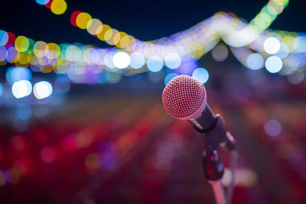 コンサートホールのマイクのクローズアップカラフルなライトとステージマイク