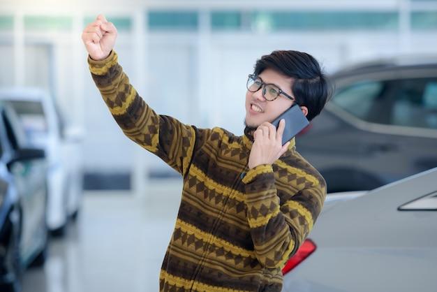 ハンサムなアジア人男性は、ショールームで新しい車を購入し、電話で話しながら幸せになり、ショールームでオンラインの良いニュースに興奮します。
