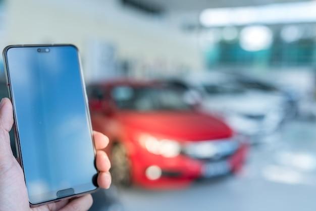 車のショールームで空白の画面を持つモバイルスマートフォンを使用して男の手