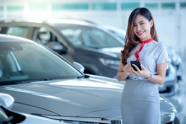 美しいアジアの女性は、ショールームで新しい車を売り、電話で話を楽しみます。ショールームでオンラインの良いニュースについて興奮しました。