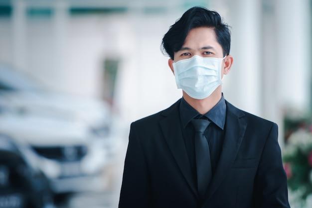 ハンサムなアジア系のビジネスマンが車の営業所にいて、彼は病気であり、ビジネスコンセプトに取り組んでいる間、彼はマスクを着用しています。