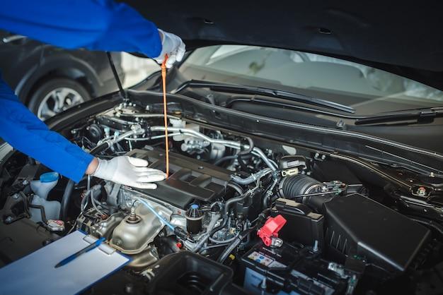 Персонал автомеханика тянет указатель уровня масла вверх, чтобы проверить уровень масла. чтобы проверить состояние автомобиля