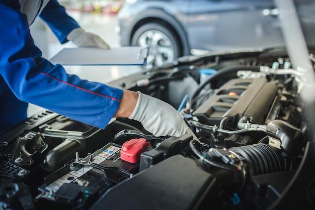 Обрезанное изображение красивый механик в форме работает в автосервисе. ремонт и обслуживание автомобилей.