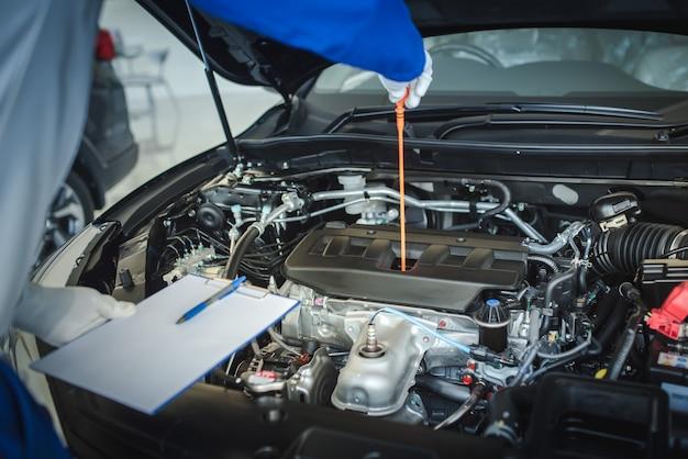 自動車整備士がオイルレベルゲージを引き上げて、オイルレベルを確認しています。車の状態を確認するには