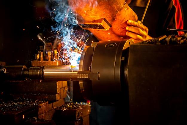 Сварщики в защитной одежде и металлических трубах сваривают маски на промышленных столах, пока искры летят. закрыть сверла и лом в промышленных магазинах