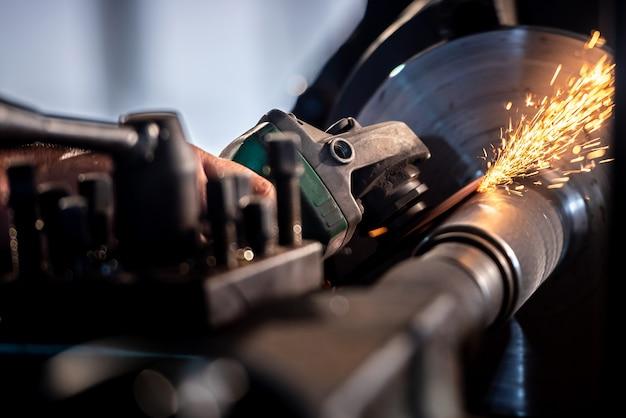 メカニックは、工場の鉄骨構造に電気砥石を使用しています。