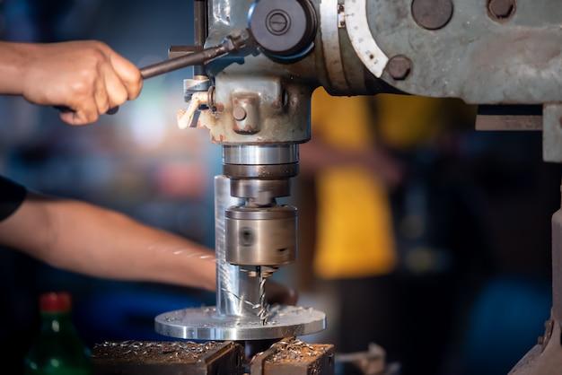Рабочие используют стальные сверла в токарных цехах, буровые установки и металлические сверла на промышленных предприятиях для сверления металла.
