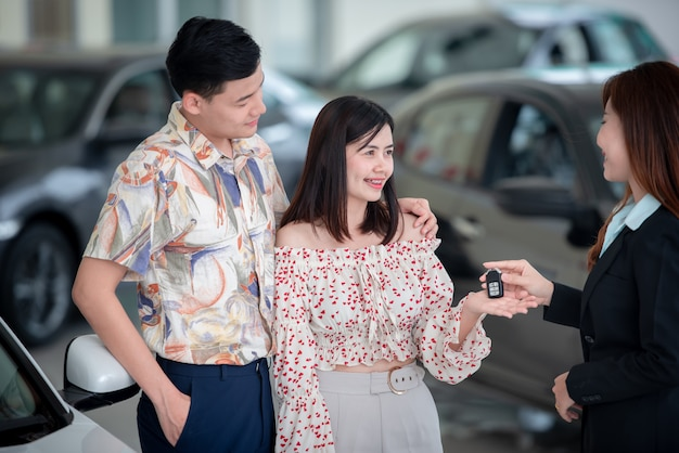 若いアジアの愛好家は、ディーラーで新車を購入し、車のディーラーと一緒に車を購入して喜んでいます。