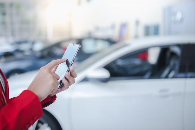 車のセールスマンアジアの女性がスマートフォンを保持