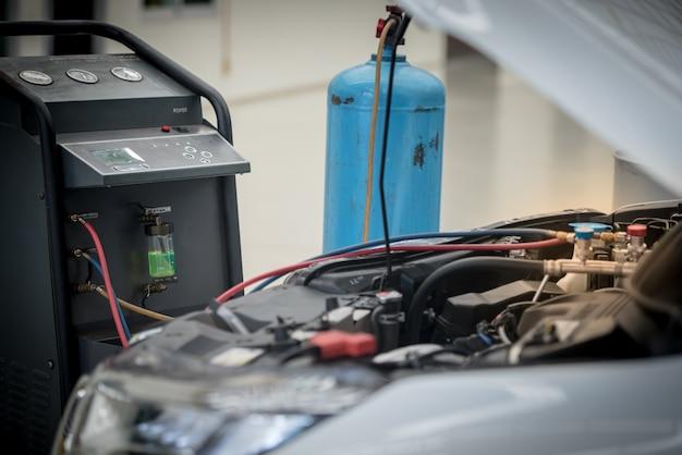 カーエアコンの整備。サービスステーション。自動車修理。自動車整備士圧力と漏れを確認してください。空調システム用
