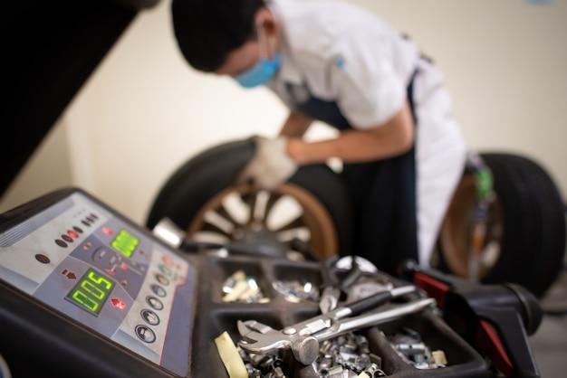 サービス技術者は、メンテナンスサービスを備えたバランシングマシンを使用してタイヤを交換しています。