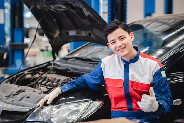 彼のガレージで快適に笑っているアジアの自動車整備士の写真。修理センターと自動車修理センターを含む自動車サービス。