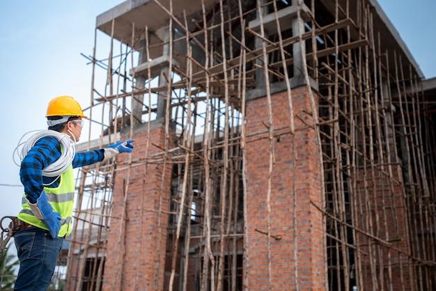 アジアの監督者や請負業者は、大きな家や進行中の作業現場の建設を監視しています。