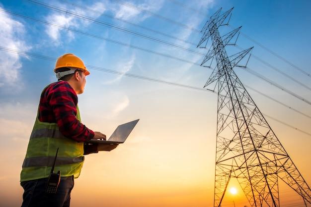 発電所に立っているノートブックコンピューターを使用して、高電圧電極で電気エネルギーを生成することによって計画作業を確認している電気技師の画像