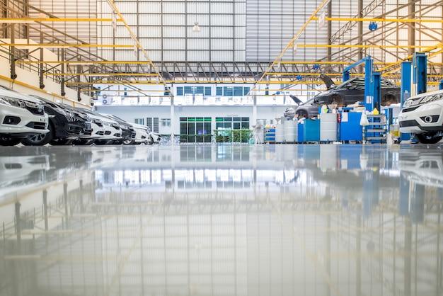 インテリアカーケアセンター。新車工場サービスのエポキシ床に置かれたサービス中の車の電気リフト