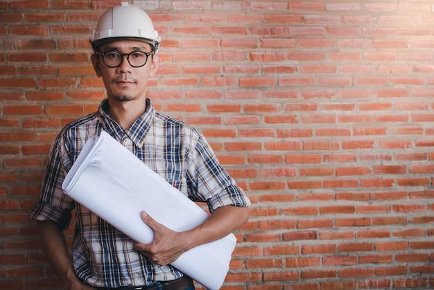 Азиатский инженер-строитель или архитектор стоя, держа бумагу в стиле архитектурного проекта на строительной площадке в оранжевом фоне