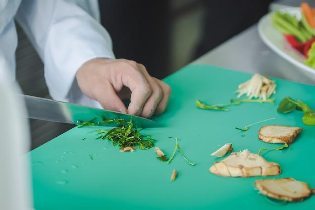 Шеф-повар нарезает овощи на еду собирается готовить на кухне, чтобы подать еду клиентам в ресторане отеля