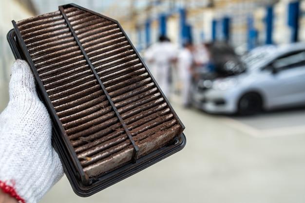 車の汚れたエアフィルターを保持している技術者